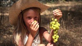 Niño que come las uvas, pequeño granjero hambriento Girl Eats Fruits en Olive Orchard 4K