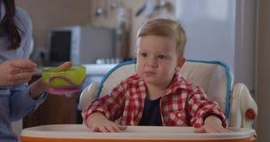 Niño que come los alimentos para niños que se sientan en una silla y una madre que alimentan con una cuchara almacen de metraje de vídeo