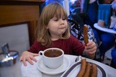 Niño que come los bastones con el chocolat Fotos de archivo