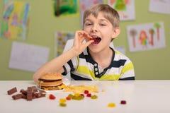 Niño que come los dulces y comida rápida imágenes de archivo libres de regalías