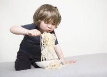 Niño que come los espaguetis en el sofá Foto de archivo