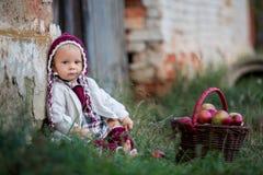 Niño que come manzanas en un pueblo en otoño Pequeño juego del bebé fotos de archivo