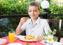 Niño que come microprocesadores Foto de archivo