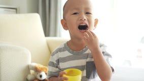 Niño que come soplos del cereal almacen de metraje de vídeo