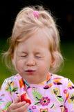 Niño que come una fresa en el jardín Imagen de archivo
