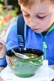 Niño que come una sopa imagenes de archivo
