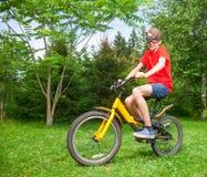 Niño que completa un ciclo al aire libre Imagen de archivo libre de regalías