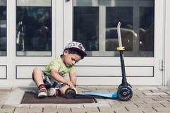 Niño que comprueba una vespa Fotografía de archivo libre de regalías