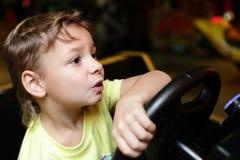 Niño que conduce un simulador del coche foto de archivo