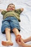 Niño que consigue el pie cosquilleado Fotos de archivo