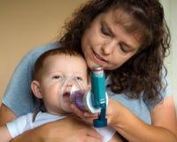 Niño que consigue el tratamiento de respiración de madre Imágenes de archivo libres de regalías