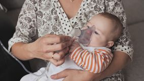 Niño que consigue el tratamiento de respiración de madre mientras que sufre de enfermedad almacen de video