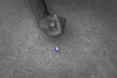 Niño que consigue listo para tirar durante el juego de mármol imagenes de archivo
