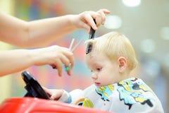 Niño que consigue su primer corte de pelo imagen de archivo