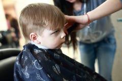 Niño que consigue un corte de pelo Imagen de archivo