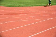 Niño que corre en pista en el estadio Fotos de archivo libres de regalías