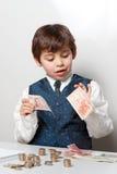 Niño que cuenta el dinero Imagen de archivo