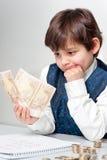 Niño que cuenta el dinero Imagenes de archivo