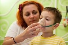 Niño que cuida de la madre con la inhalación de los aerosoles Foto de archivo libre de regalías