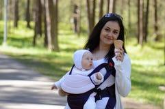 Niño que cuida de la mujer en portador de bebé foto de archivo