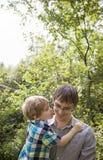 Niño que da a padre un beso Imagen de archivo
