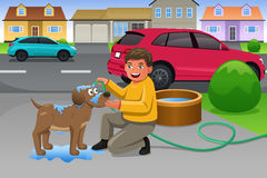Niño que da a su perro un baño Imagenes de archivo