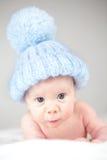Niño que desgasta el sombrero azul del knit Fotografía de archivo