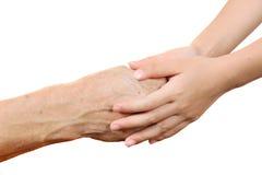 Niño que detiene a la mujer mayor mayor por las manos aisladas en la pizca Imagen de archivo