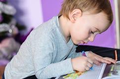 Niño que dibuja en casa Imagen de archivo libre de regalías