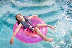 Niño que disfruta de jugar en la piscina fotos de archivo