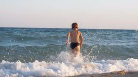 Niño que disfruta de vacaciones en la costa y del funcionamiento en el mar para nadar almacen de metraje de vídeo