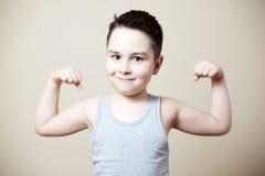 Niño que dobla el bíceps Fotografía de archivo