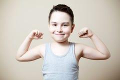 Niño que dobla el bíceps Imagen de archivo