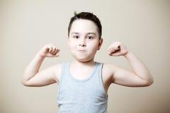 Niño que dobla el bíceps Imagen de archivo libre de regalías