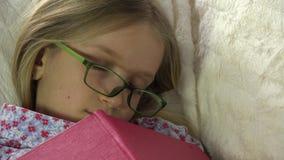 Niño que duerme después del libro de lectura, caída dormida en su cama, muchacha del niño en casa metrajes