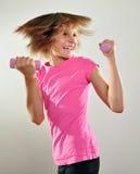 Niño que ejercita con pesas de gimnasia Fotos de archivo libres de regalías