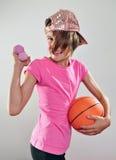 Niño que ejercita con pesas de gimnasia y la bola Foto de archivo