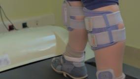 Niño que ejercita en la rueda de ardilla con el estímulo eléctrico en las piernas almacen de metraje de vídeo
