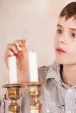 Niño que enciende velas con la llama en partido Imagen de archivo