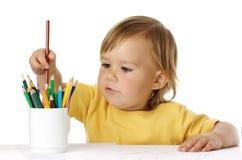 Niño que escoge un creyón de la taza fotografía de archivo libre de regalías