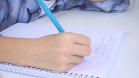 Niño que escribe, estudiando, niño pensativo, estudiante pensativo que aprende, colegiala en sala de clase almacen de metraje de vídeo