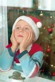 Niño que espera un Santa detrás de la ventana Fotos de archivo
