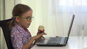 niño que estudia en el ordenador portátil, muchacha de las lentes 4K que juega a los videojuegos en Internet almacen de metraje de vídeo