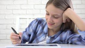 Niño que estudia en la tableta, muchacha que escribe en la clase de escuela, aprendiendo haciendo la preparación metrajes