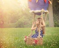 Niño que finge volar en globo del aire caliente afuera Fotos de archivo