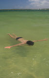 Niño que flota en laguna del paraíso Fotografía de archivo libre de regalías