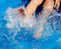 Niño que golpea con el pie en piscina Imagen de archivo