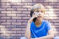 Niño que habla en el teléfono celular Concepto de la gente, de la tecnología y de la comunicación Foto de archivo libre de regalías
