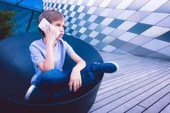 Niño que habla en el teléfono celular en la calle Fotografía de archivo