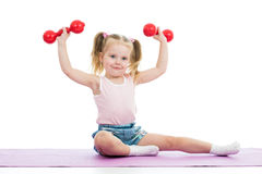 Muchacha del niño que hace ejercicios con pesas de gimnasia Imagenes de archivo